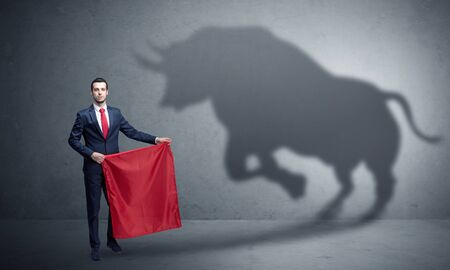 Businessman standing with red cloth in his hand and big bull shadow on the wall