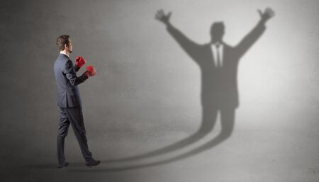 Businessman with boxing gloves fighting with disarmed businessman shadow