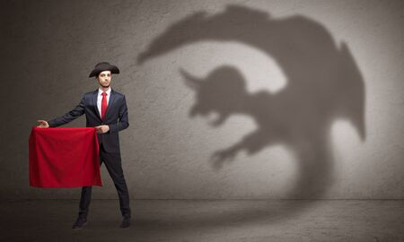 Businessman standing with red cloth in his hand and imp shadow on the background Standard-Bild