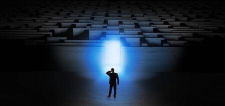 Businessman getting ready to enter the dark labyrinth with illuminated door Archivio Fotografico