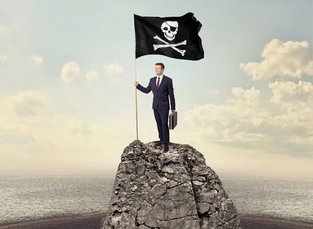 Successful businessman on the top of a mountain holding pirate flag