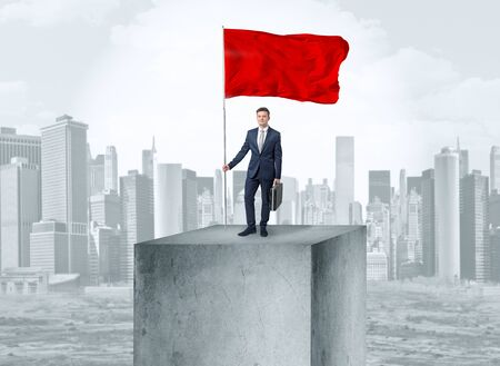 Handsome businessman on the top of the city with red flag