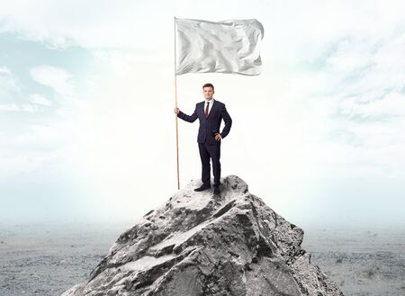 Handsome businessman on the top of the mountain with white flag Фото со стока