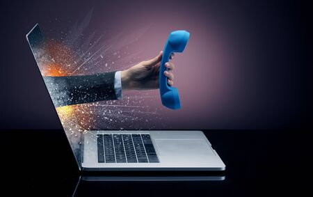 Hand with vintage phone coming out of a laptop with sparkling effects