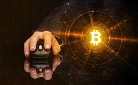 Hand using wireless mouse with cryptocurrency concept on dark background
