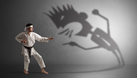 Young karate man fighting with a big black scary shadow 스톡 콘텐츠