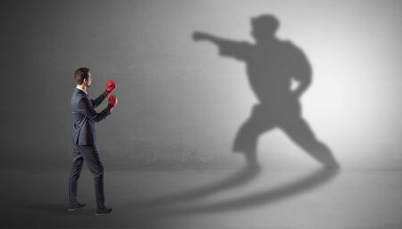 Businessman fighting with his strong karate man shadow