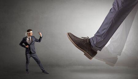 Big foot treading small young karate man Standard-Bild