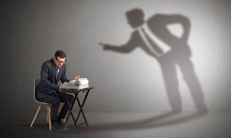 Hombrecito trabajando y una gran sombra discutiendo con él Foto de archivo
