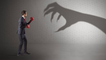 Tiny businessman fighting with scary hand shadow
