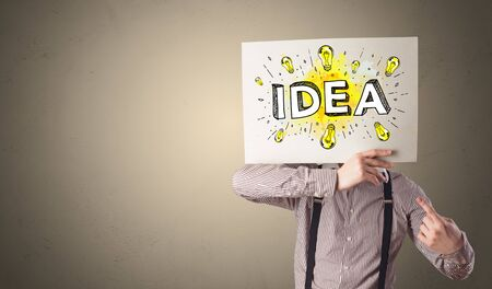 Young person holding white paper with new idea concept in front of his head