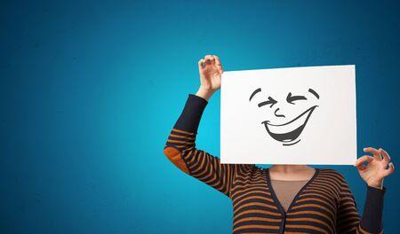 Persona casual sosteniendo un papel con un emoticon genial frente a su cara