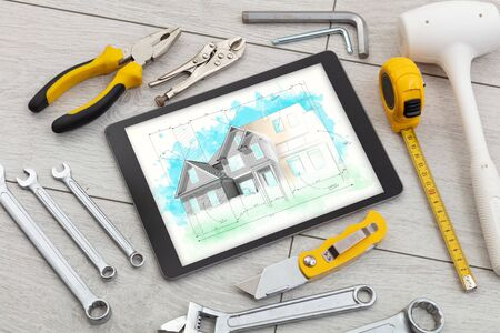 Tablet with construction tools and house plan concept Imagens