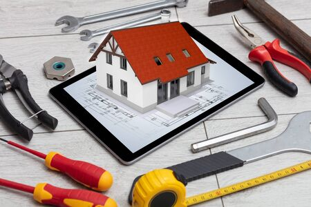 Tablet with construction tools and 3d home plan concept Imagens