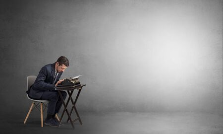 Man working hard on a typewriter in an empty space