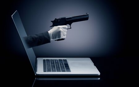 Hand with gun coming out of a laptop with sparkling effects Banco de Imagens