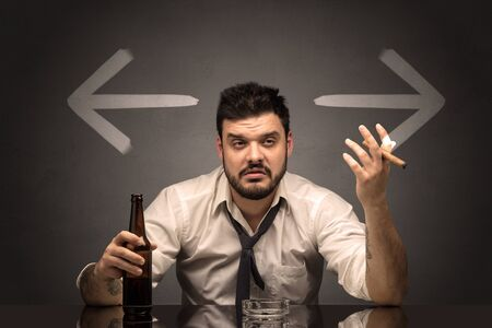 Drunk disappointed man sitting at table with arrows around Stockfoto