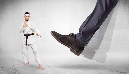 Big foot trample young karate trainer concept 写真素材 - 128877369