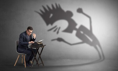 Man working hard and he is afraid of a yelling shadow Stock Photo