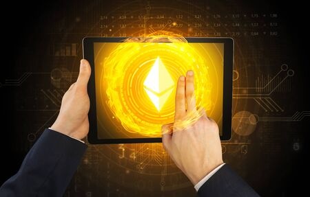Elegant hand touching tablet with cryptocurrency concept Banco de Imagens
