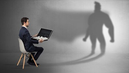 Humble businessman staying and offering stuffs to a superhero shadow Stock Photo