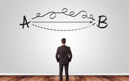 Homme d'affaires recherchant la connexion entre deux choses tout en se tenant devant un mur Banque d'images