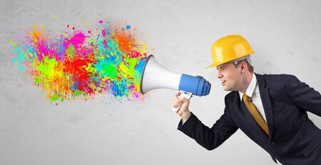 Young architect constructor yelling with megaphone with and colorful splash concept Imagens