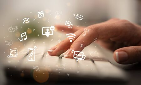 Business woman hand typing on keyboard with drawn application icons around Reklamní fotografie