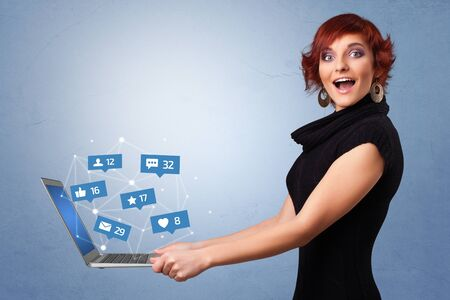 Woman holding laptop with different types of social media symbols and icons