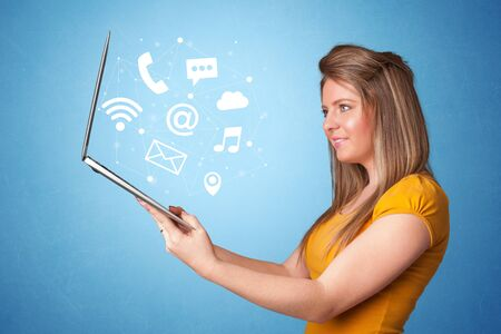 Woman holding laptop with online services symbols Stockfoto