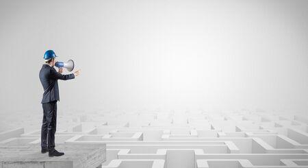 Architekt, der auf Labyrinth steht und einen zukünftigen Plan betrachtet