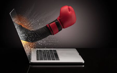 Hand with boxing gloves coming out of a laptop with sparkling effects Stock Photo