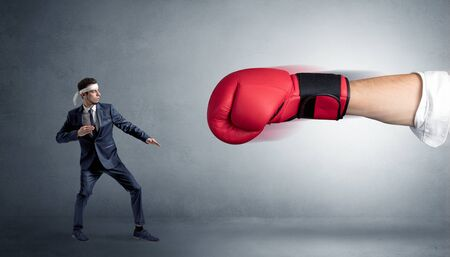 Little man fighting with a giant red boxing glove