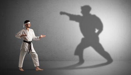 Young karate man confronting with his own shadow Imagens