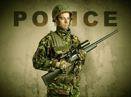Uniformed armed soldier with damaged wall background Stockfoto