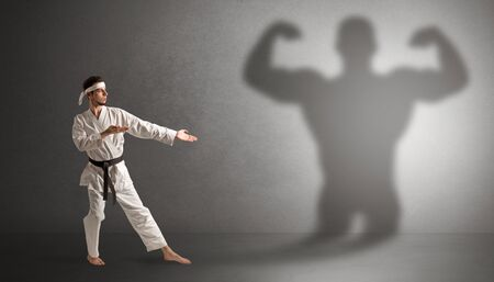 Young karate man fighting with a big black scary shadow Archivio Fotografico - 129151229