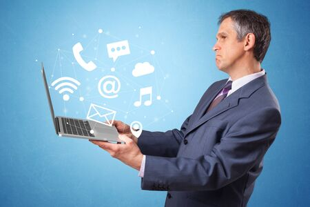 Man holding laptop with online services symbols