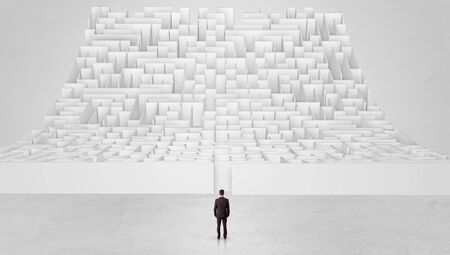 Businessman standing and thinking in front of a curved infinity maze