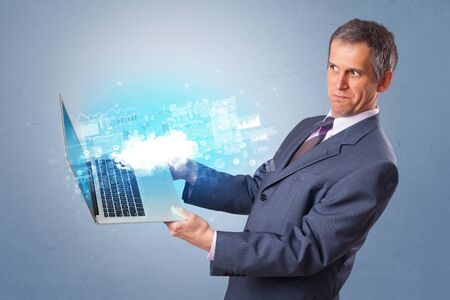 Man holding laptop projecting notifications, symbols and information based on cloud technology system