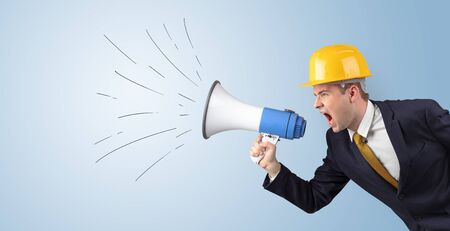 Young architect constructor yelling with megaphone and copyspace Standard-Bild - 129152575