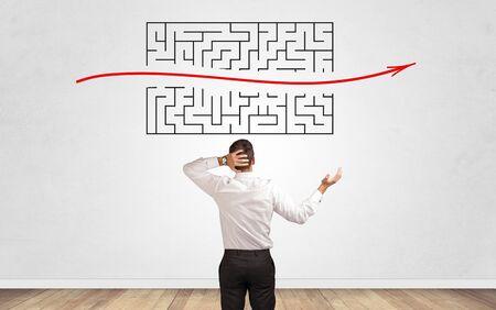 Geschäftsmann im Zweifel, der zu einem Labyrinth schaut und den Ausweg sucht Standard-Bild