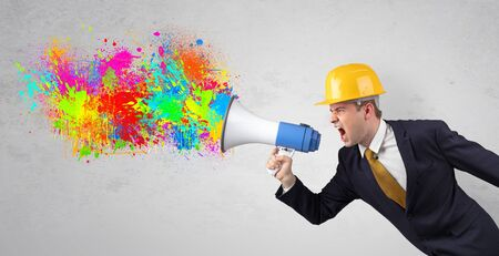 Young architect constructor yelling with megaphone with and colorful splash concept Standard-Bild - 129153410