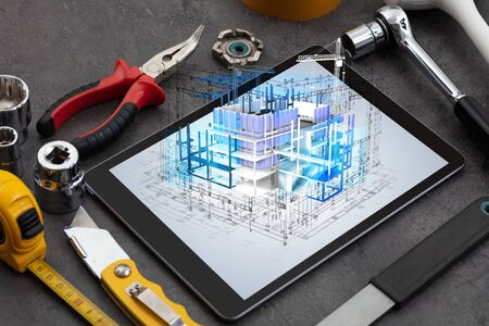 Tablet with construction tools and 3d house plan concept Фото со стока