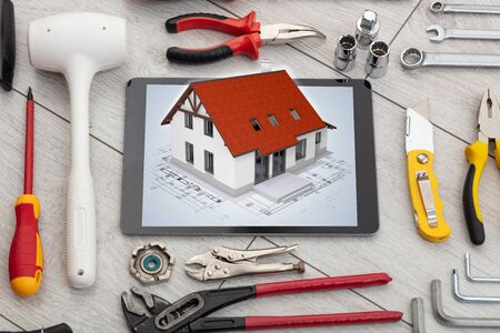 Tablet with construction tools and 3d home plan concept Фото со стока