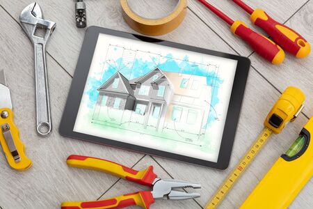 Tablet with construction tools and house plan concept Фото со стока