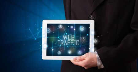 Young business person working on tablet and shows the digital sign: WEB TRAFFIC