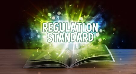 REGULATION STANDARD inscription coming out from an open book, educational concept Stock Photo