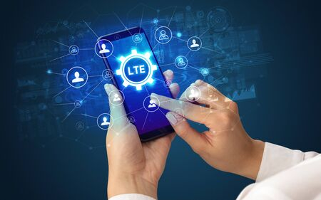 Female hand holding smartphone with LTE abbreviation, modern technology concept Stock fotó