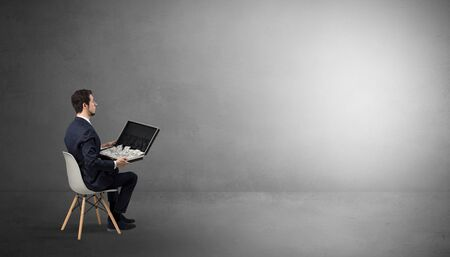 Businessman staying in an empty grey dark room with stuffs on his lap