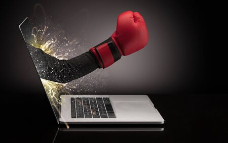 Hand with box gloves coming out of a laptop with sparkling effects Stock Photo